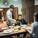 Teruyuki Kagawa et al. sitting at a table eating food