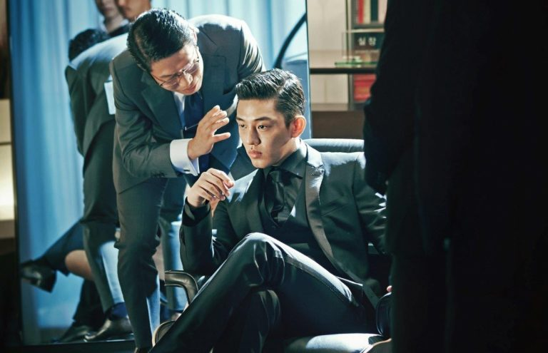 Yoo Ah-in sitting in a chair talking on a cell phone