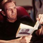 Ralph Fiennes sitting on a table