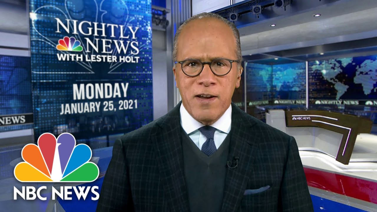 Lester Holt in a suit standing in front of a store