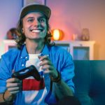 A man in a blue shirt and sitting on holding video game re